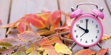 Web banner of daylight savings time, alarm clock and leaves