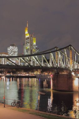 Embankment, river, bridge and city at night. Frankfurt am Main, Germany