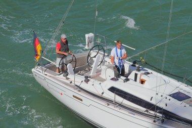 Warnemunde, Rostock, Germany - Jul 06, 2018: Two men steer yacht in sea