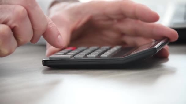 Hand of businessman using calculator, close-up