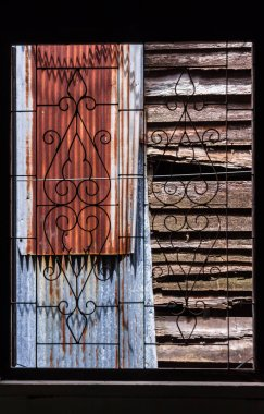 Abstract vintage wrought iron pattern window and zinc roof with wood fence background.