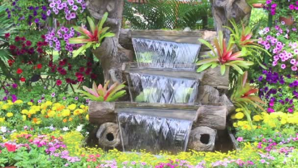 Záběry vodopádů a živých květů dekorace v útulném květinových zahradách v létě.