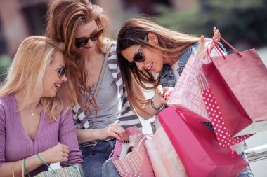 young women having fun and walking after shopping in city