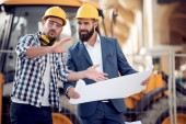 technický tým plánování stavebních prací, hledá papír plány na staveništi.