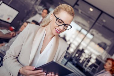 Young blonde businesswoman in glasses using digital tablet in modern office.
