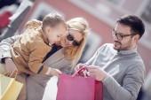 Fényképek Eladó, a fogyasztás és az emberek koncepció-boldog család kis gyermek, és a város bevásárló táskák