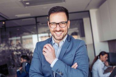 Handsome smiling confident businessman portrait in modern office.