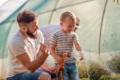 Fotografie Junger Vater mit seinem Sohn bei der Gartenarbeit