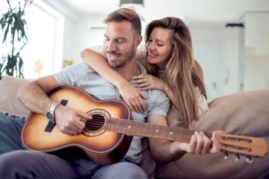 Young couple in love sitting on the sofa while young man playing guitar.