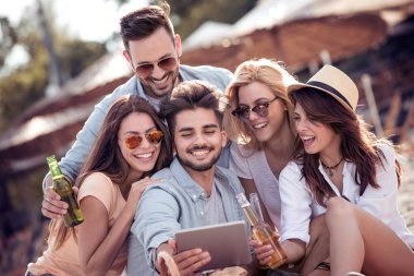 Friends drinking beer and having fun at beach party.Summer, holidays, vacation, happiness and people concept. Group of friends taking selfie with tablet