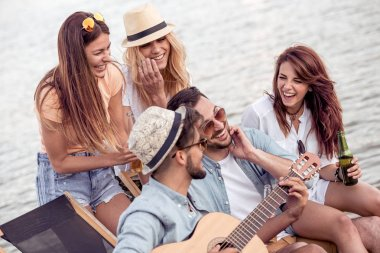 Group of friends with guitar having fun on the beach.Summer,holidays,vacation,music and people concept.