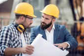 Two engineer builders with plan at construction site.