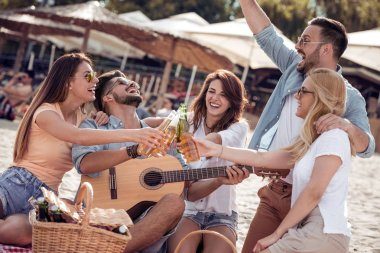 Friends drinking beers and listening to music.Having fun at beach party.Summer, holidays, vacation, music, happy people concept.