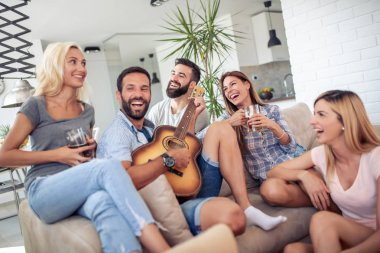 Friends having party at home,playing guitar and enjoying together.