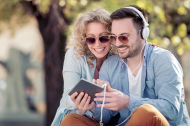 young couple using tablet and listening to music on street