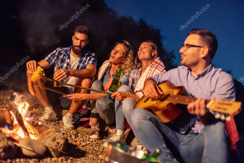 Group of friends sitting by the fire at night, grilling sausages and having great time on the beach.
