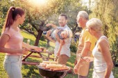 Čas strávený s rodinou. Rodina na dovolené s barbecue party v jejich zahradě