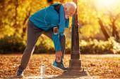 Senior runner in nature.Attractive senior man jogging in the park.