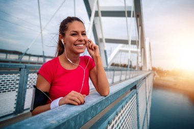 Young fitness woman jogging on bridge in the morning.