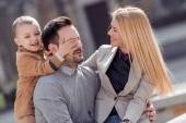 Boldog fiatal család, város, utca, szórakozás.