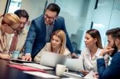 Plné soustředění v práci. Skupina podnikatelů, kteří spolu pracují a komunikují, zatímco sedí u kancelářského stolu.