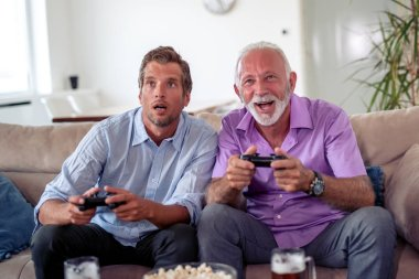 Focused on game.Portrait of two excited men playing video games at home. stock vector