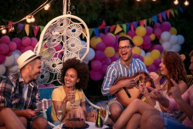 Party, holidays, celebration and people concept.Smiling friends celebrate birthday at night party.