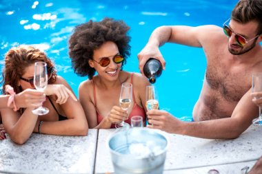 Happy young friends with wine enjoying in pool party.