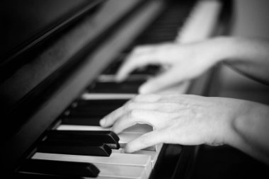 Close up of two hands playing piano, shallow focus. Black and white