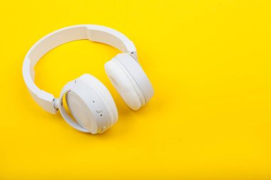 Wireless white headphones on yellow background. Music concept. Earphones on yellow background.
