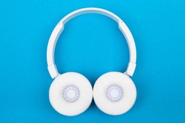 Wireless white headphones on blue background. Music concept. Earphones on blue background.