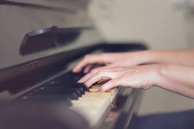 Close up of two hands playing piano, shallow focus.