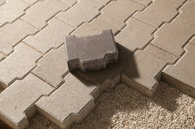 Building an pedestrian path with paver bricks. Sidewalk pavement
