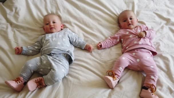 Two girls sisters lie on the bed. Two baby twins on the bed