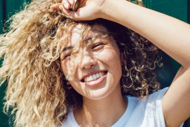 Portrait of a smiling young woman with curly hair and freckles.