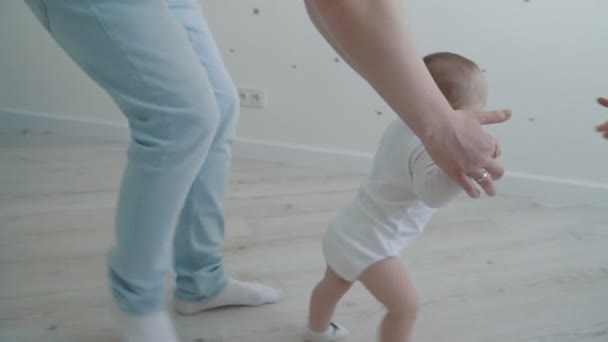Happy little baby boy making first steps on white floor with the help of his father. Slow motion family concept video.