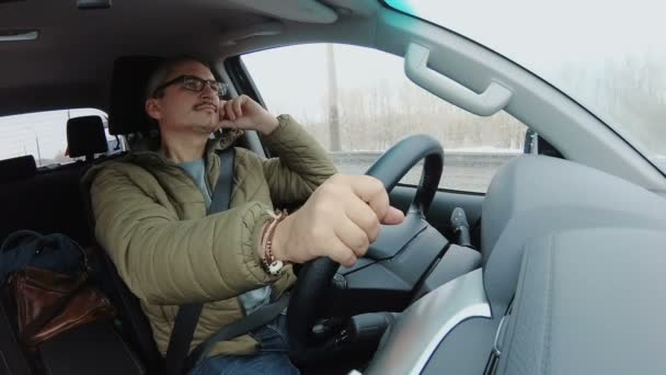 Serious longhaired man driving car with one hand, traveling during bad weather in spring. People stock footage shot at spring season time.
