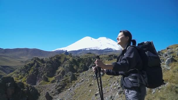 Hiker woman with backpack admiring Elbrus mountain view landscape from the cliff edge. Enjoying nature vacation travel adventure at Caucasus mountains.