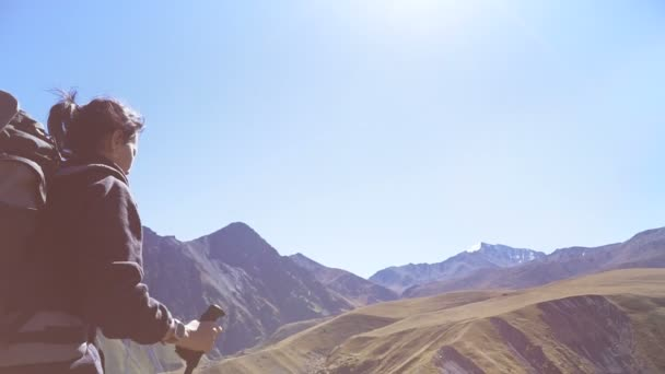 Hiker woman with backpack raising hands admiring Elbrus mountain view landscape from the cliff edge. Enjoying nature vacation travel adventure at Caucasus mountains. Slow motion video.