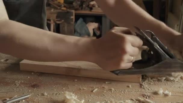 Zručný řemeslník tesař ořezávátek obrobku Dřevěná deska s jack letadlo v dílně. Výroba ručně vyrobený nábytek.