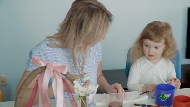 Kellemes húsvéti ünnepeket! Anya és vele a kis lányom húsvéti tojásfestés kosarat és a tojás az ünnepi asztalnál. Lassú mozgás