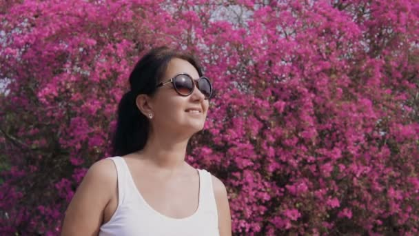 Woman in blooming garden. Portrait of attractive smiling woman enjoying blossom smell in spring park.