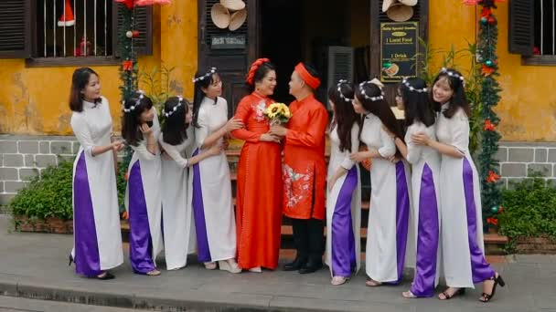 HOI AN, VIETNAM - JANUARY 6, 2019: Street scene with local vietnamese wedding - bride and groom are photographed with friends on the street.
