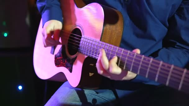 Man playing an acoustic guitar at concert. Hands of a man playing the brass strings of a guitar. Musician clamps the chords on the guitar frets.