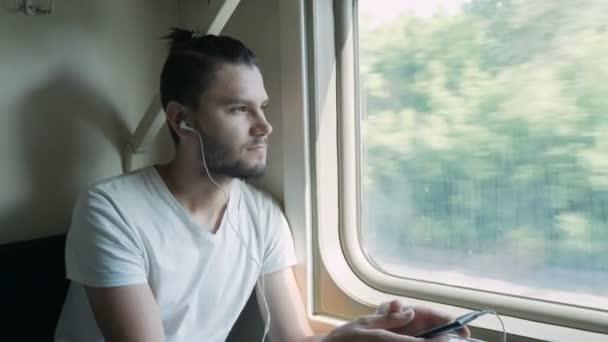 Unavený, smutný mladý muž jedoucí vlakem. Poslech hudby, podcastu nebo audiobooku při jízdě vlakem a při pohledu do okna. Ruční snímek.