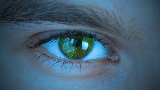 Zblízka na lidské oko s planetou země se točí. Řízení a ochrana osob, kontrola a bezpečnost v technologii přístupu. Stylizované modré chladné odstínu barvy.