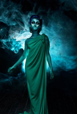 Halloween image of young siren or mermaid standing in green dress in front of the twilight fog.