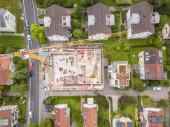 Letecký pohled na staveniště v rezidenční části města ve Švýcarsku s velkým jeřábem.