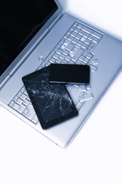 A silver laptop with a broken keyboard, tablet with a cracked display and black phone. A close-up picture of part of broken laptop and cracked screen on a tablet.
