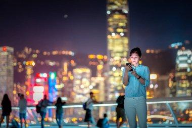 Young woman using smarphone in Hong Kong city street at night stock vector